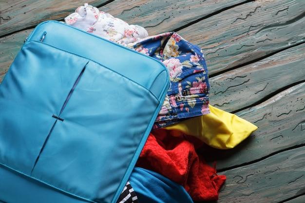 Синий чемодан переполнен одеждой. вещи торчат из чемодана. бери все, что тебе нужно. упаковка вещей перед отпуском.