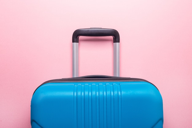 Blue suitcase on pastel pink. creative summer holidays, vacation, travel concept
