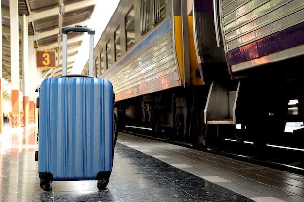 Blue suitcase on the train platform.