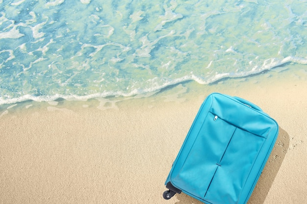 Blue suitcase with water waves on the sandy beach