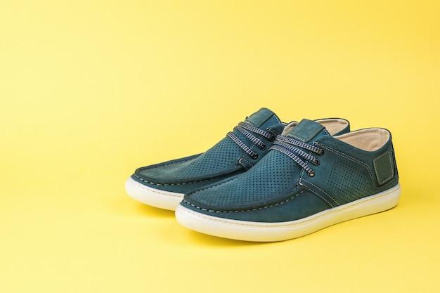 노란색 배경에 흰색 발바닥과 푸른 여름 남자 신발. 편안한 여름 남성 신발.