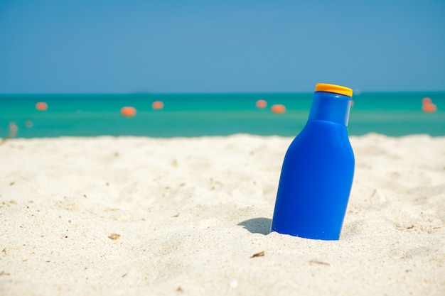 Blue sun block bottle on the beach sand
