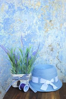 ギリシャの古いひびの入った壁に青い帽子とラベンダーの花