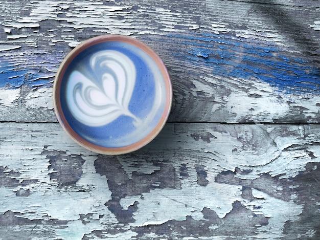 高齢者の素朴な木のトレンディな再利用可能な竹のコーヒーカップにハート柄の青いスーパーラテ