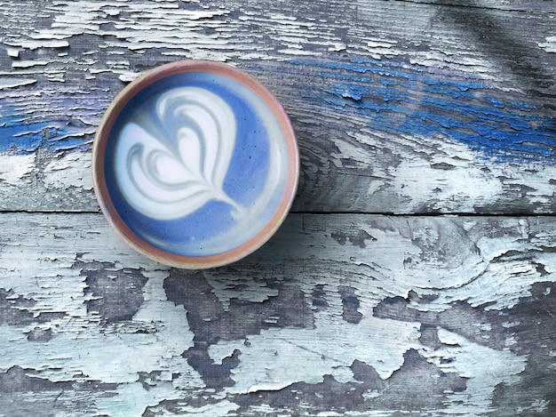 Blue super latte with heart pattern in trendy reusable bamboo coffee cup on aged rustic wood