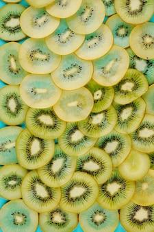 얇은 달콤한 키위 조각, 건강한 식생활 개념으로 덮여 파란색 표면