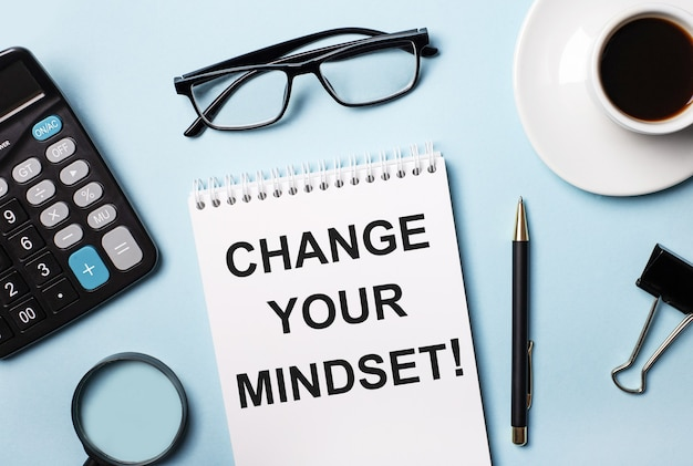 On a blue surface, glasses, calculator, coffee, magnifier, pen and notebook with the text change your mindset
