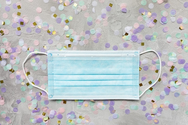 Blue surgical mouth mask and colorful confetti