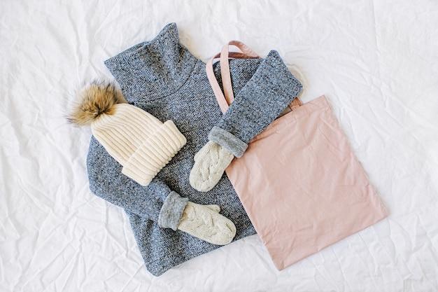 帽子とトートバッグが付いている青いセーター。白い背景の秋/冬の服のコラージュ。上面図フラットレイ。