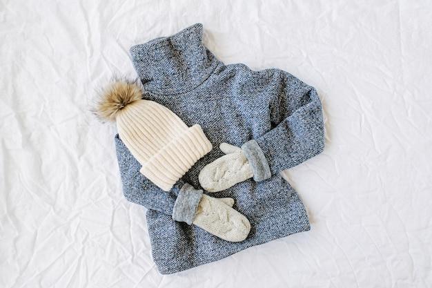 帽子と青いセーター。白い背景の上の秋/冬のファッションの服のコラージュ。上面図フラットレイ。
