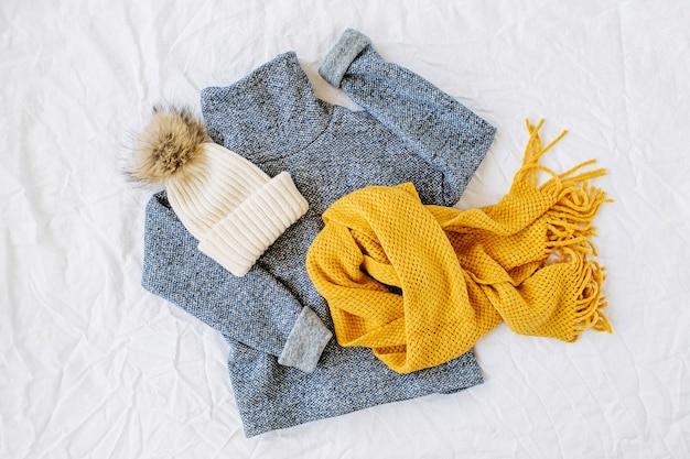 黄色のニットスカーフと帽子が付いた青いセーター。白い背景の上の秋/冬のファッションの服のコラージュ。上面図フラットレイ。