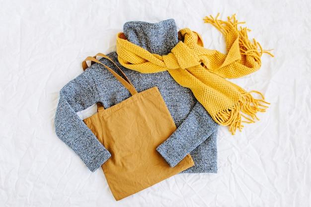 黄色のニットスカーフとトートバッグが付いた青いセーター。白い背景の上の秋/冬のファッションの服のコラージュ。上面図フラットレイ。