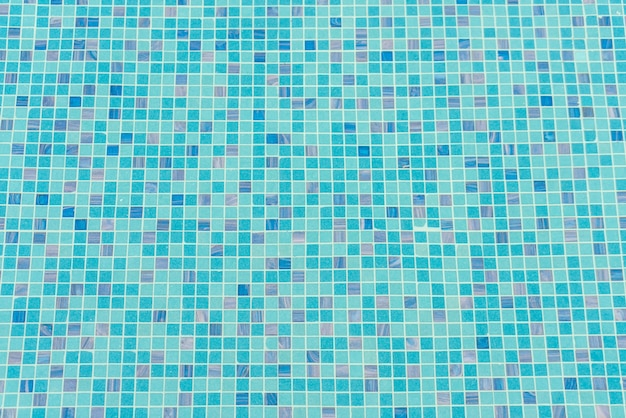 Blue swimming pool rippled water .