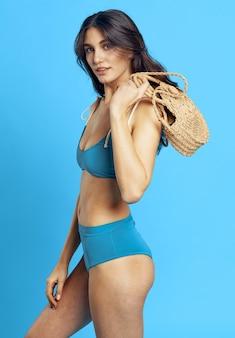 Blue swimsuit beach bag posing fashion summer. high quality photo