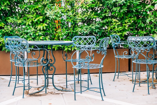 A blue table and chair made of metal of a summer cafe in the street.
