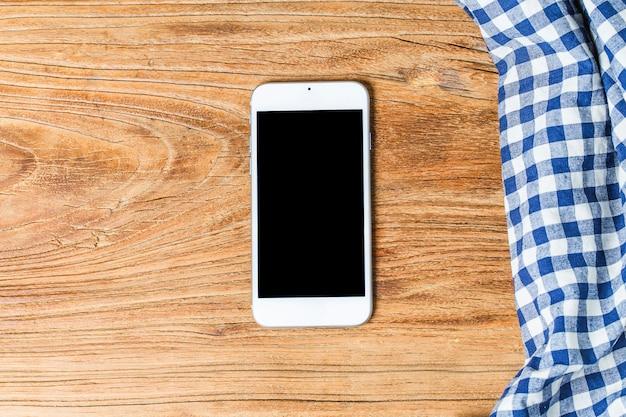 Panno di tabella blu su sfondo bianco, copia spazio, vista superiore.mobile telefono