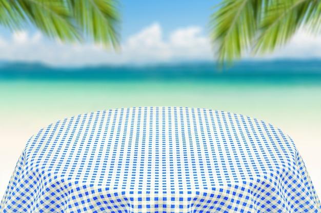 ビーチの背景がぼやけた青いテーブルクロス。プレーンテキストまたは製品の背景