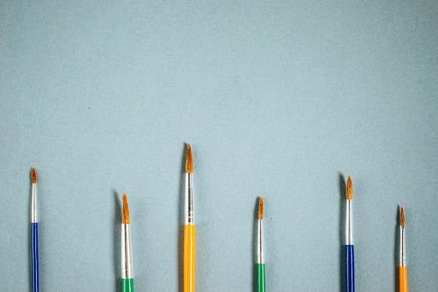 蓝色的桌子上放着画笔