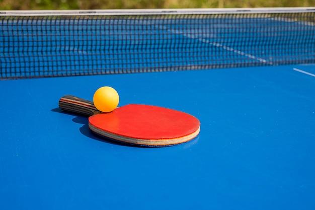 青い卓球またはピンポン屋外タブレットテニスクローズアップピンポン卓球ラケットと青いテニステーブル上のボール用アクセサリースポーツ