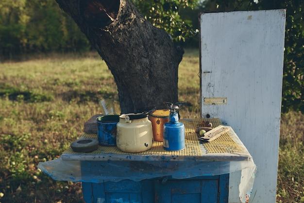 自然の中で木の近くに銀行とヴィンテージのドアと青いテーブル