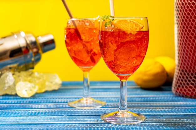 Blue table with two glasses of the refreshing aperol spritz cocktail with mint and orange leaves
