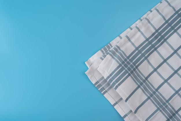 파란색 배경에 파란색 식탁보 텍스트 위쪽 보기를 위한 복사 공간이 있는 새 주방 수건 w
