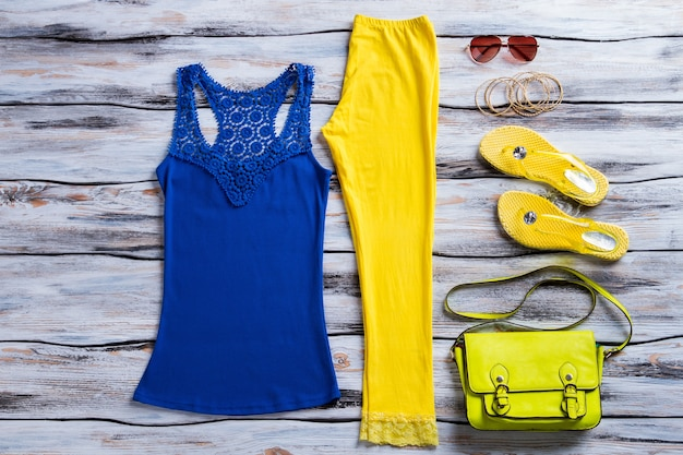 Blue tank top and trousers. colorful pants with flip flops. female outfit with stylish sunglasses. summer clothing sold at discount.