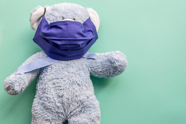 Blue teddy bear in a dark blue reusable mask on a mint plain background. place for text on the right. medecine.