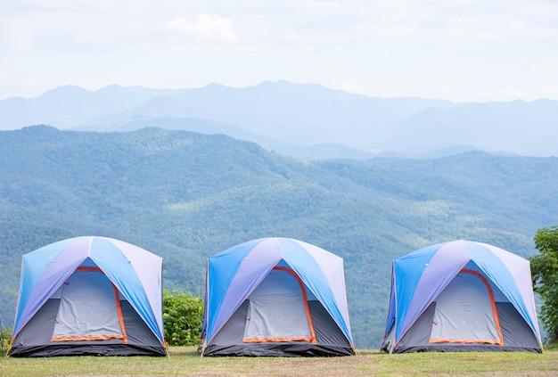 青いテントが芝生の山々と空に3軒の家を並べました。