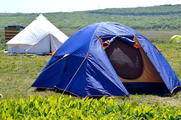 キャンプの芝生の上の青いテント