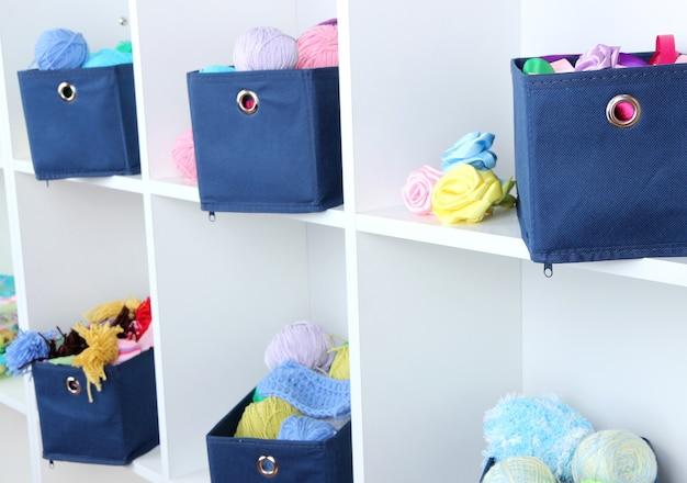 白い棚に糸が入った青いテキスタイルボックス
