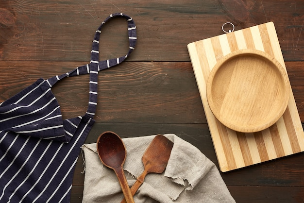 白い縞模様の青いテキスタイルキッチンエプロンと台所用品