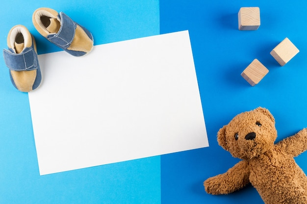 Blue theme background with blank card, teddy bear, wooden blocks and baby shoes