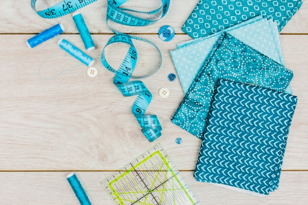 Blue thread; measuring tape; buttons; ruler and folded print clothes on wooden desk