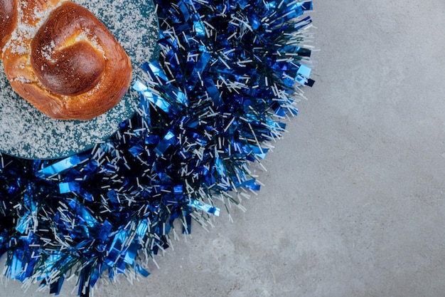 Blue tinsel circle with a bun in the middle on marble table.