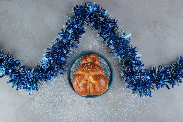 Blue tinsel in a zig-zag next to a sweet bun on marble table.