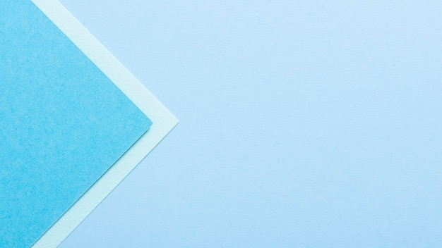 Blue toned triangular paper sheets with copy space
