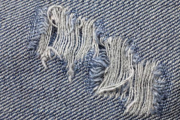 Синяя рваная структура джинсов из денима.