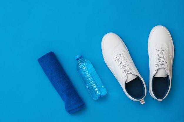 Синее полотенце, белые кроссовки и бутылка с водой. спортивный стиль. плоская планировка. вид сверху.