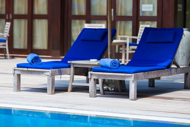 Blue towels on loungers near swimming pool at tropical resort