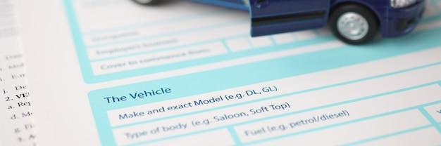 保険文書のクローズアップタイプの自動車保険の概念の上に立っている青いおもちゃの車