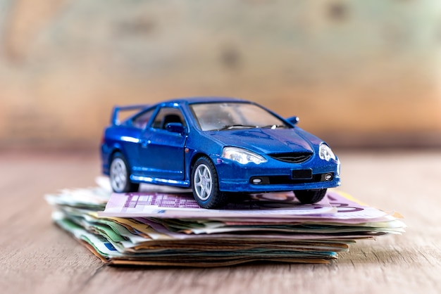 Blue toy car with euro bills on desk