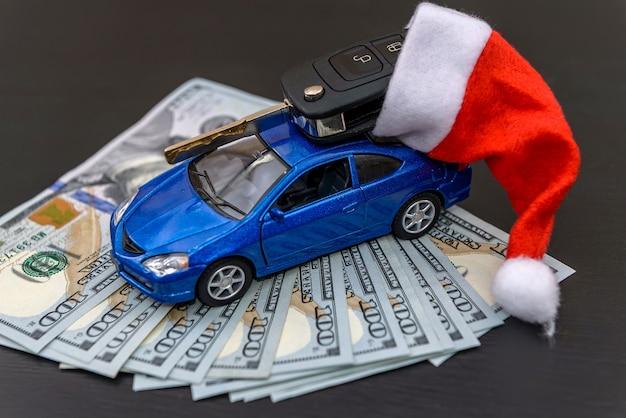 Синий игрушечный автомобиль с настоящим ключом и шляпой санта-клауса