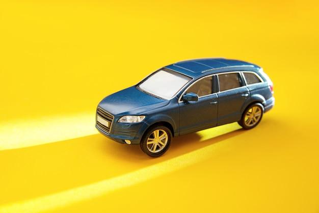 長い太陽の影と黄色の背景に青いおもちゃのオフロード車。スペースをコピーします。配達、タクシー、休暇のコンセプト。