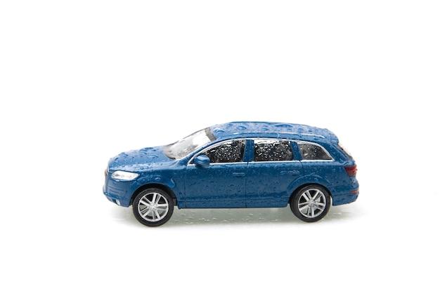 흰색 배경에 고립 된 비 방울과 파란색 장난감 오프로드 차량. 세차 된 차. 공간을 복사하십시오.