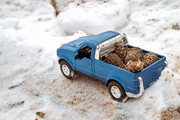 제재소의 파란색 장난감 픽업 트럭 눈 더미와 톱밥에 갇힌 뒤 차체에 전나무 원뿔 운반