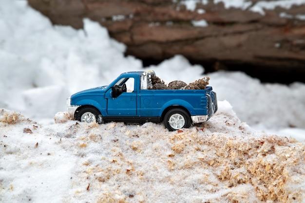 제재소에 있는 파란색 장난감 픽업 트럭 눈 더미와 톱밥에 갇힌 뒤에 전나무 콘을 싣고