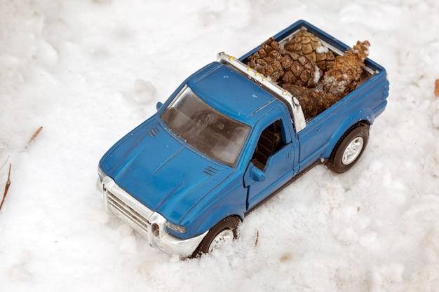 도로의 겨울 숲에 있는 파란색 장난감 픽업 트럭 차체 뒤쪽에 전나무 콘을 싣고