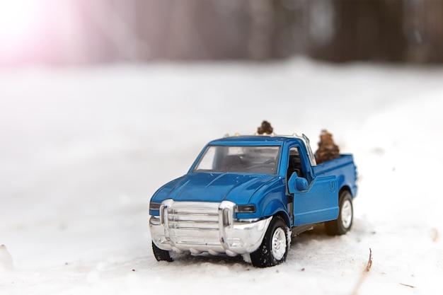 문이 열린 도로의 겨울 숲에 있는 파란색 장난감 픽업 트럭