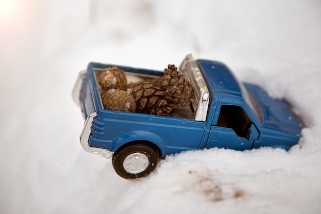눈 더미에 갇힌 파란색 장난감 픽업 트럭 차체 뒤쪽에 전나무 콘을 싣고